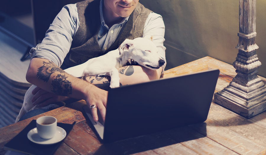 Smiling tattooed man in eyeglasses working at home on laptop while sitting at the wooden table with cute dog sleeping on his hands.Adult guy using modern computer for surfing web.Horizontal