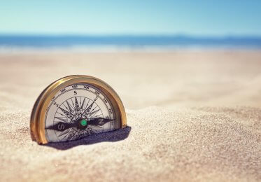 A concept image of a compass in the sand.