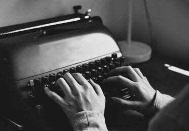 Two hands working on a typewriter.