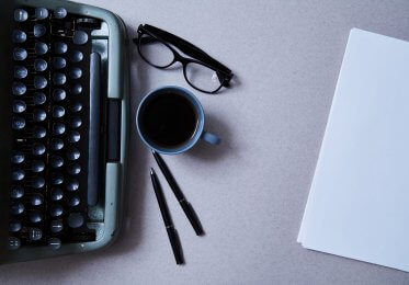 Concept of an old typwriter with coffee and reading glasses.