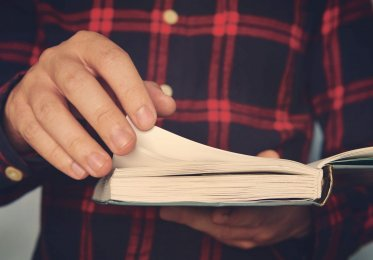 man-holding-book-turning-pages