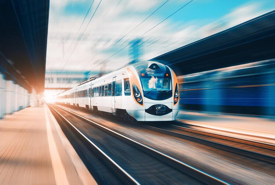A speeding passenger train leaving a station