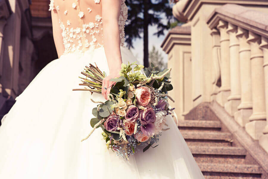 Bride stood on steps wearing white lace and tulle wedding dress holding bouquet of flowers
