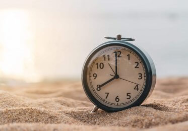 Concept image of time to interactive. A small clock sits in front of a rising sun.
