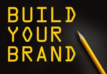 "A stylish sign that states ""build your brand"" written in pencil."