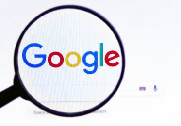 A magnifying glass inspects the Google logo.