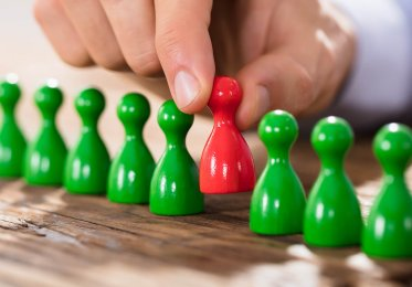 hiring concept image with green and red wooden figures