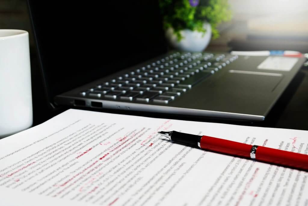 proofreading on paper with a laptop and pen