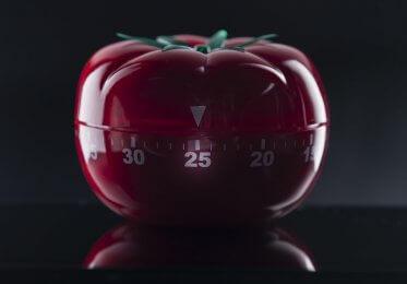 A mechanical timer, shaped like a tomato, sits on a counter top.